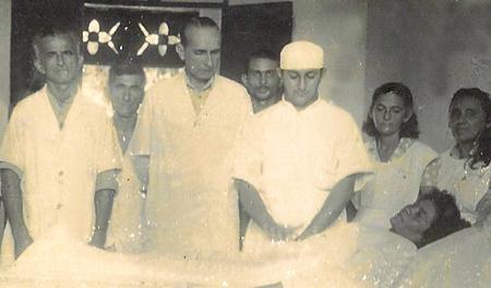 O médico e a mesma equipe de enfermeiros observam uma paciente recém-operada