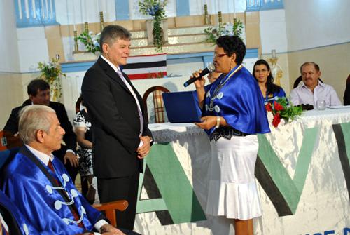 A acadêmica Vitória Santos entrega a placa ao médico-cirurgião